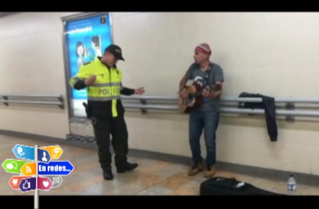 Policía y cantante callejero en estación de TransMilenio